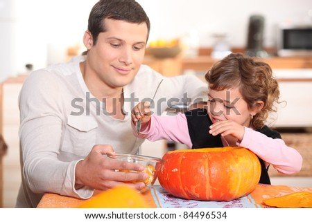 Dad and daughter hollowing out a pumpkin - stock photo