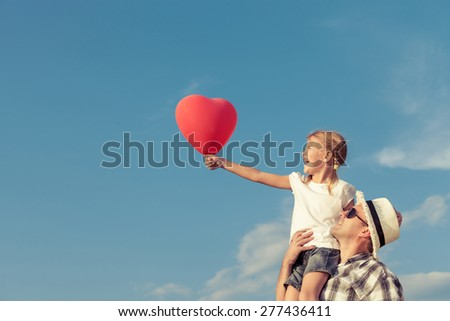 Dad and daughter in sunglasses with balloon playing near a house at the day time. Concept of friendly family. - stock photo