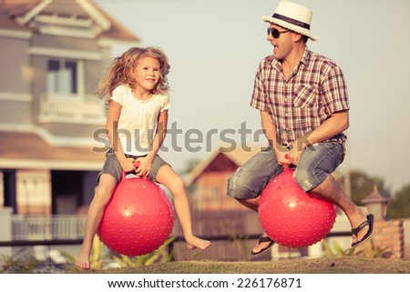 Dad and daughter jumping on inflatable balls on the lawn in front of house at the day time - stock photo