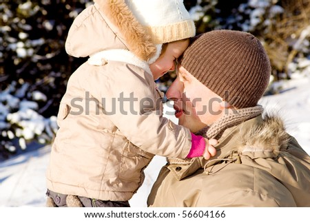 Dad and daughter playing in winter park - stock photo
