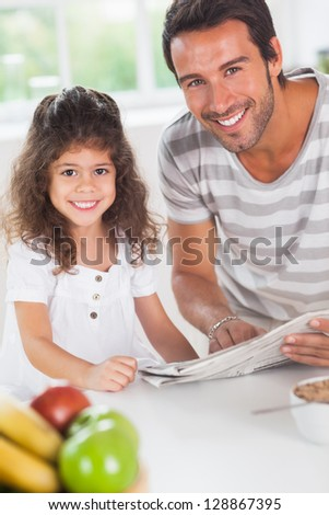 Dad and daughter reading a newspaper during breakfast in kitchen - stock photo