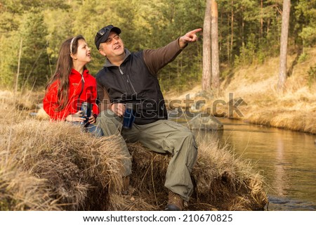 Dad and daughter resting beside a stream and chat.  - stock photo