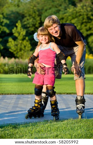 Dad and daughter rollerskating in park - stock photo