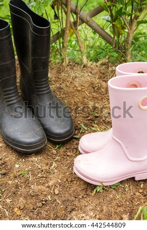Dad and girl gardening boots in garden. Relationship and activity of family. Agriculture background. - stock photo