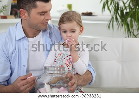 Dad and his daughter eating marshmallows - stock photo