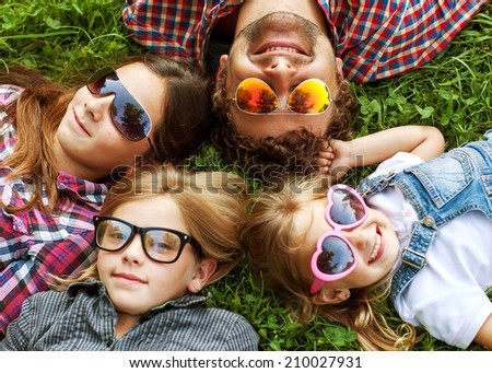 Dad and his 3 daughters lie on the grass in sunglasses happy. hipster Style - stock photo