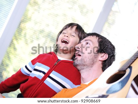 Dad and his kid singing with guitar at home - stock photo