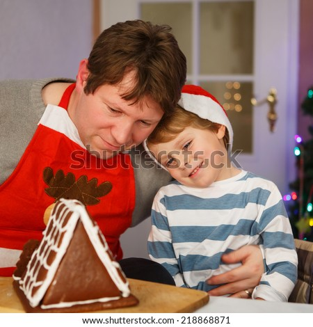 Dad and his little adorable child having fun with baking a gingerbread cookie house at christmas time, home's kitchen - stock photo