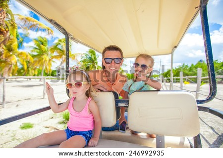 Dad and his little girls driving golf cart on tropical beach - stock photo