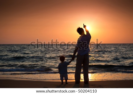 dad and his little son standing on the beach and looking at sunset - stock photo
