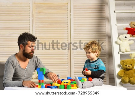Dad and kid build of plastic blocks. Father and son with busy faces create colorful constructions with toy bricks. Family and childhood concept. Man with beard and boy play on wooden wall background