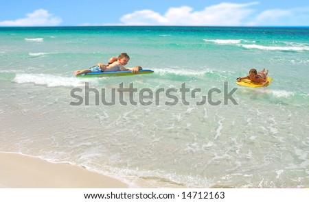 Dad and kids playing in beach surf on boards - stock photo