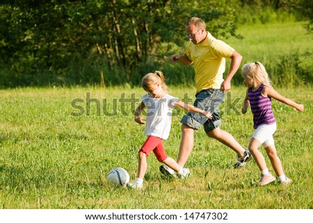 Dad and little daughters playing soccer on a green meadow - stock photo