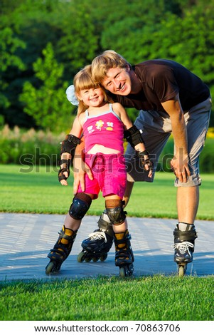 Dad and preschool daughter in roller skates - stock photo