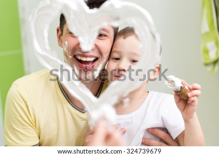 Dad and preschooler son child draw heart shape on mirror with shaving foam playing in bathroom - stock photo