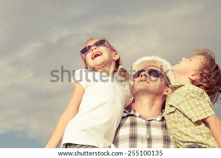 Dad and son and  daughter playing near a house at the day time.  - stock photo