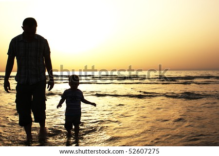 Dad and son at sunset - stock photo