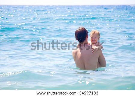 dad and son bathing together in the sea - stock photo