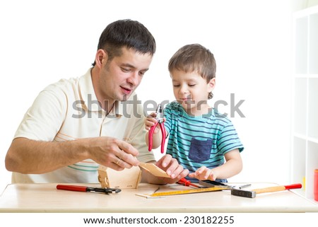 Dad and son child working with tools - stock photo