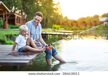 Dad and son fishing in summer - stock photo