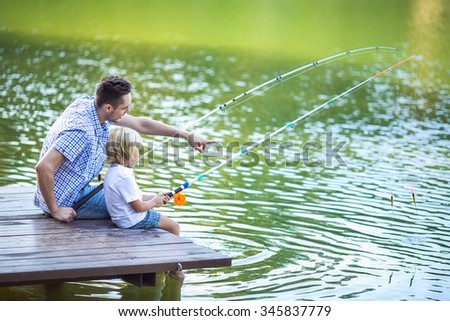 Dad and son fishing outdoors - stock photo