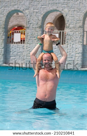 Dad and son having fun together on vacations - stock photo