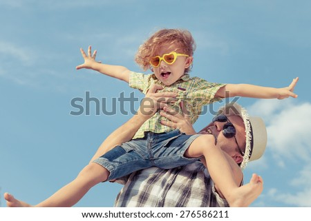 Dad and son in sunglasses playing near a house at the day time. Concept of friendly family. - stock photo