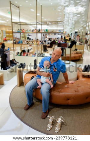 Dad and son in the shoe shop waiting mum shopping - stock photo