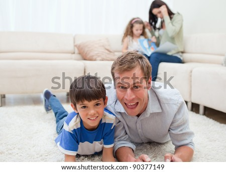 Dad and son lying on the carpet with mom and daughter behind them