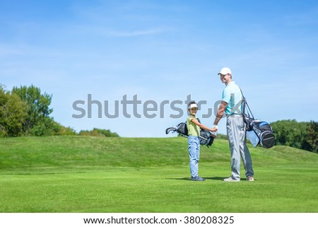 Dad and son on golf lawn