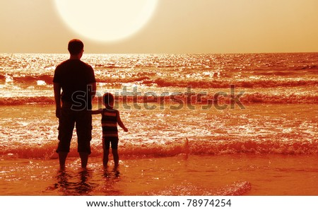 Dad and son on the beach at at sunset - stock photo