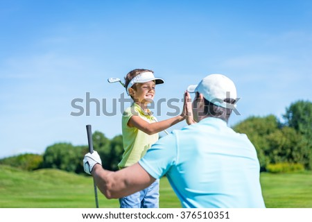 Dad and son playing golf - stock photo