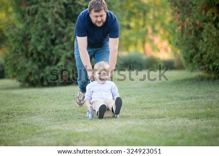 Dad and son playing, having fun together in park in summer. Father carrying his happy and excited kid in toy stroller at speed, full length - stock photo