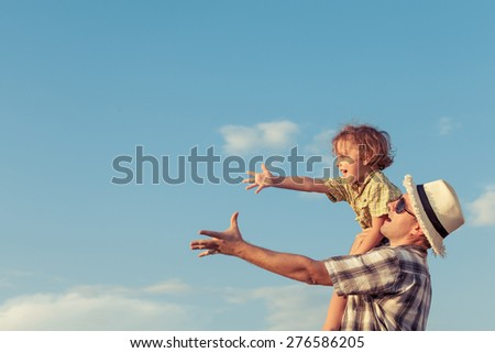 Dad and son playing near a house at the day time. - stock photo