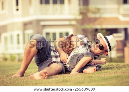 Dad and son playing on the lawn in front of house at the day time - stock photo