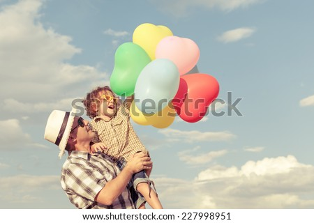Dad and son playing with balloons near a house at the day time - stock photo