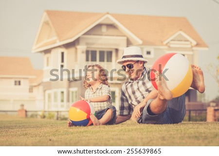 Dad and son playing with balls on the lawn in front of house at the day time - stock photo