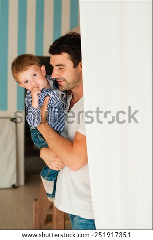 Dad and son standing near the wall and play - stock photo