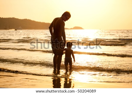 dad and son walking along the beach during the sunset - stock photo