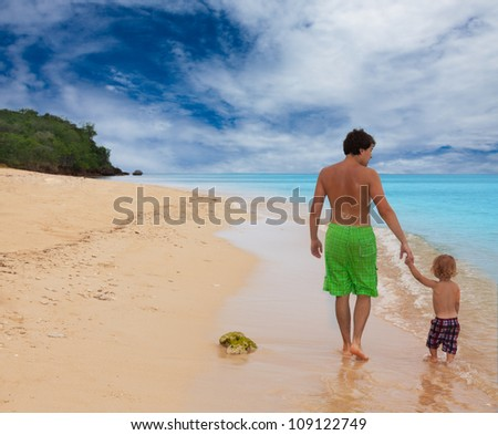 Dad and son walking on the seashore and holding hands - stock photo