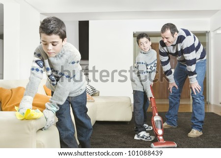 Dad and twin sons cleaning their home's living room.