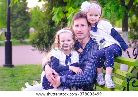 Dad and two beautiful little daughters sitting on a bench in the park and hugging on a warm spring evening. The whole family dressed in the same color scheme. Family style clothing. Family look.