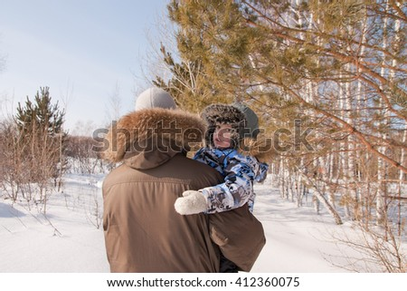 dad carries the baby in her arms for a walk along the forest in the winter