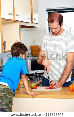 Dad chopping tomato in kitchen as young son watches - stock photo