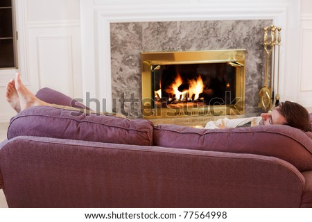 Dad dozes off by the fire - stock photo