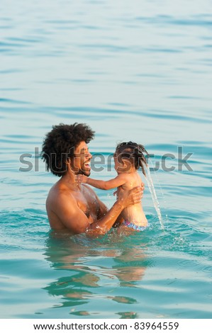 Dad fooling around with his daughter on the beach