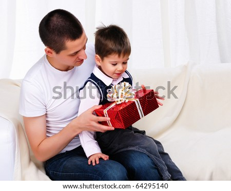 Dad gives his son a gift in red box - stock photo