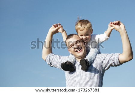 Dad giving his young son a piggy back ride as they both laugh with pleasure and enjoyment, low angle against a clear blue summer sky with copyspace - stock photo