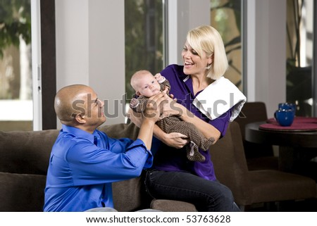Dad handing 3 month old baby to mom for feeding
