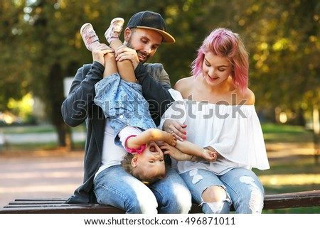 Dad has fun with his little daughter while he sits with her on the bench